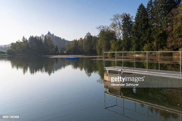 the hohes schloss castle of bad groenenbach is reflected in the natural outdoor swimming pool --bad clevers-- in the morning light, allgaeu, bavaria, germany - clevers stockfoto's en -beelden