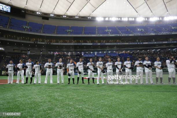 The Hokkaido NipponHam Fighters stand on the field during the anthem prior to the game against the Oakland Athletics at the Tokyo Dome on March 18...