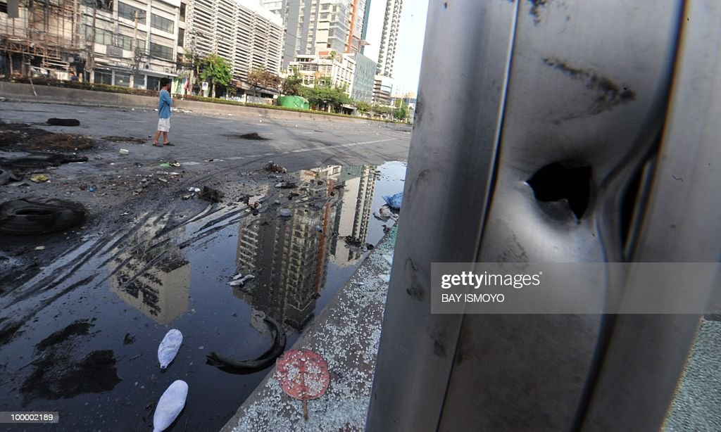 The hole created by a gunshot is seen on a pole on Rama IV boulevard in downtown Bangkok on May 20, 2010 where traces of burnt barricades and tyres remain. Plumes of smoke hung overhead as Bangkok emerged from an curfew aimed at quelling mayhem unleashed by enraged anti-government protesters targeted in an army offensive on May 2010.