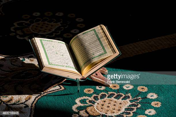 The holy book of Islam the Koran Qu'ran is open to be read in a rack standing on a green carpet inside the Sidi Saiyyed Mosque