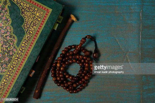 the holy quran and beads of rosary - rosary beads stock pictures, royalty-free photos & images