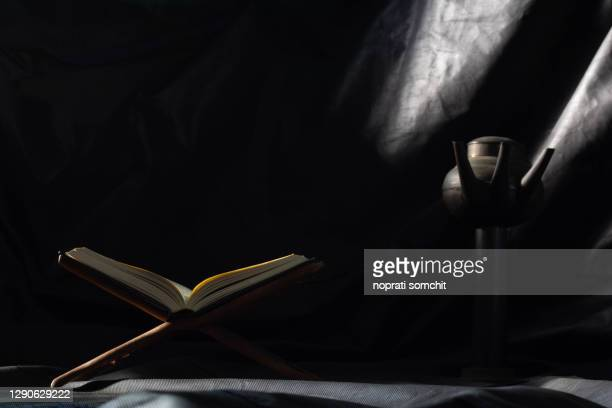the holy quran in mosque - open to read - study the black background practices of muslims around the world placed on wooden boards in low-light mosques. - salah islamic prayer stock pictures, royalty-free photos & images