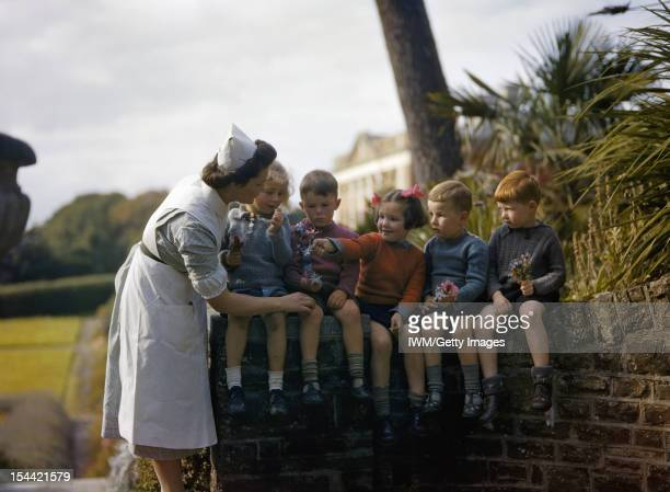 The Home Front In Britain 19391945 A nurse with child evacuees from Plymouth in the garden of the Chaim Weizmann Home at Tapley Park Instow North...
