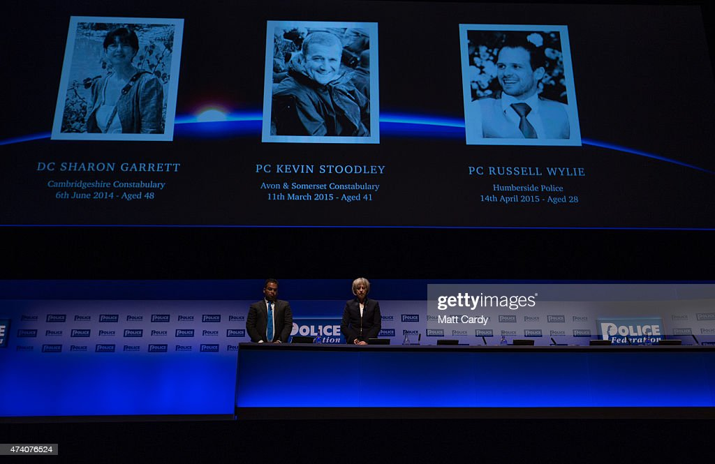 The Home Secretary, Theresa May and Krishnan Guru-Murthy (R) stand in silence as a mark of respect to fallen police officers ahead of the Home Secretary's address officers at the Police Federation annual conference on May 20, 2015 in Bournemouth, England. In her first speech since being reappointed Home Secretary, Mrs May said she wanted to stop the 'tick box culture' of policing and warned officers to 'stop crying wolf' as she spoke at the Bournemouth International Conference centre.