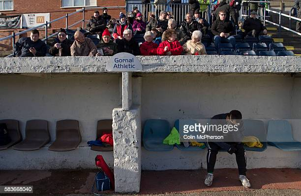 The home team's reserve goalkeeper sitting in the dugout while supporters in the seats waiting for the match to start at Garden Walk Stadium prior to...