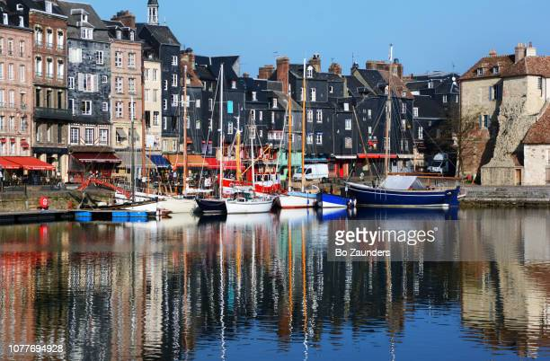The Honfleur harbor, with houses and boats reflected in the water, in Normandy, France.n t