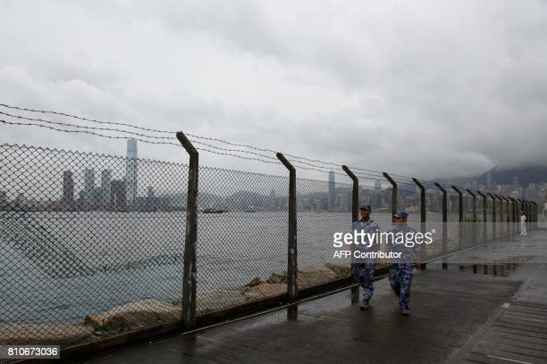 The Hong Kong skyline is seen in the background as Chinese People's Liberation Army Navy sailors walk alongside the perimeter fence of the Ngong...