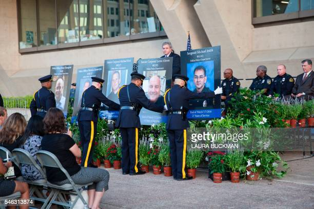 The Honor Guard places five large portraits of the officers killed in last week's sniper shooting targeting police during a Dallas Strong candlelight...