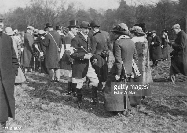 The honourable S G Pelham in conversation with female companions at the 1st Cavalry Brigade PointtoPoint meeting held at Hawthorn Hill Berkshire...