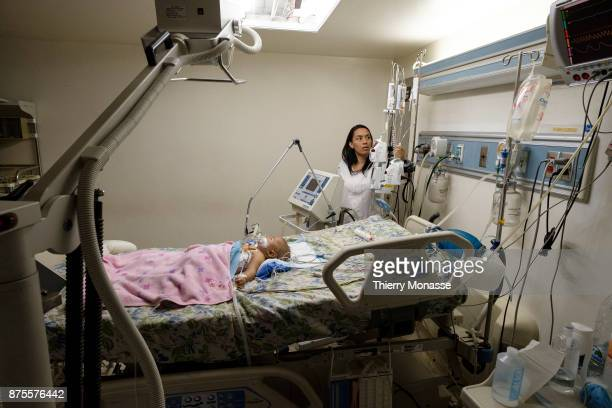 The hospital J M de los Rios Doctor and technician take care of a baby who sleeps on an adult bed