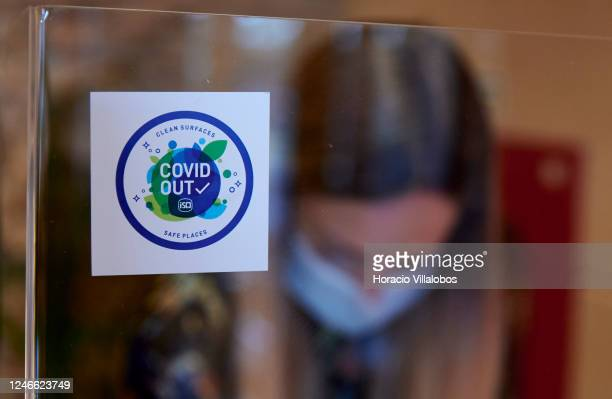 The hostess of recently reopened Estoril Mandarim Restaurant in Casino Estoril is seen wearing her protective mask behind a plexiglass panel while...