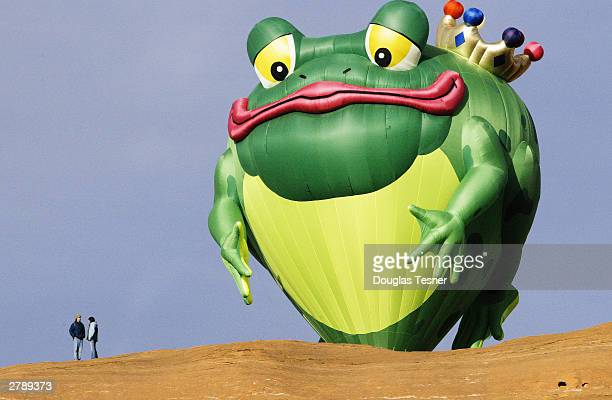 The hot air balloon Hopper T Frog from Park City Utah peeks over the red rock cliffs during the 23nd Annual Red Rock Balloon Rally at Red Rock State...