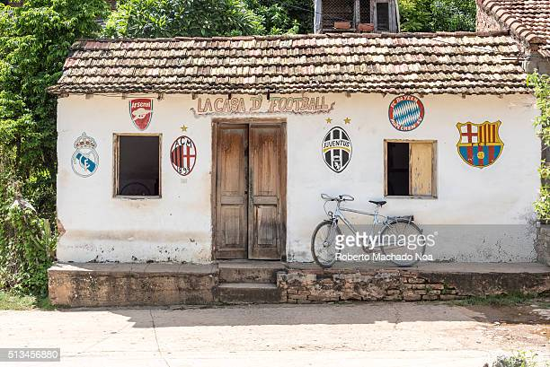 The house of soccer or football Old tile roof house with painted professional teams soccer league logos