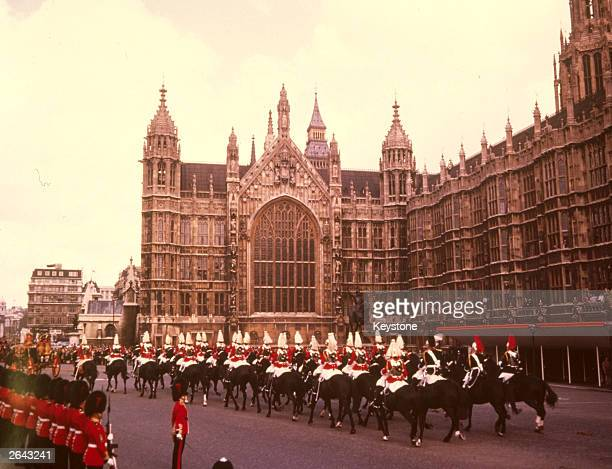 The Household Cavalry riding past the Houses of Parliament London during the state opening of Parliament