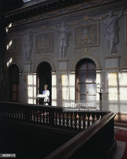 The housekeeper of Houghton Hall Norfolk 1990s Roman figures adorn the wall behind her