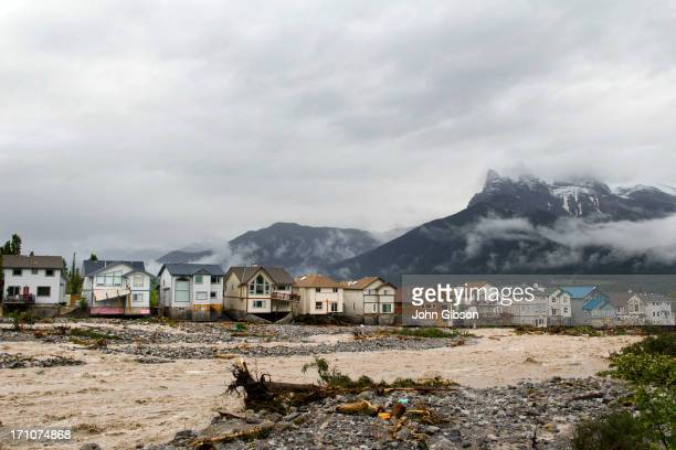 The houses along the east side of Cougar Creek in front of Three Sisters Mountain suffer damage on June 21 2013 in Canmore Alberta Canada Widespread...