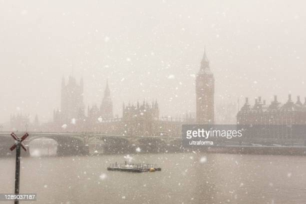 the houses of parliament during a snowstorm in london - politics and government stock pictures, royalty-free photos & images