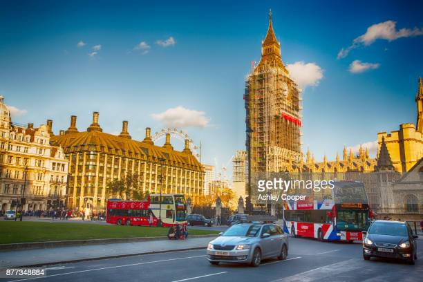 the houses of parliament, london, uk with scaffolding round big ben and tourist buses going past. - ben cooper stock-fotos und bilder