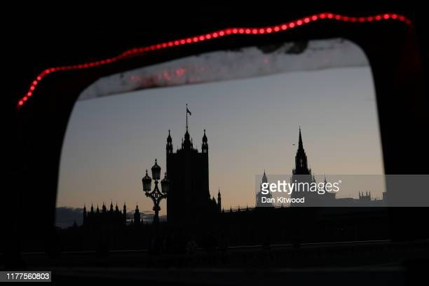 The Houses of Parliament seen through a rickshaw window are silhouetted against an evening sky on October 22 2019 in London England Prime Minister...
