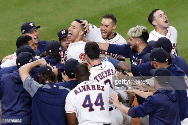 The Houston Astros celebrate with Carlos Correa after his walkoff solo home run in the 11th inning in game two of the American League Championship...