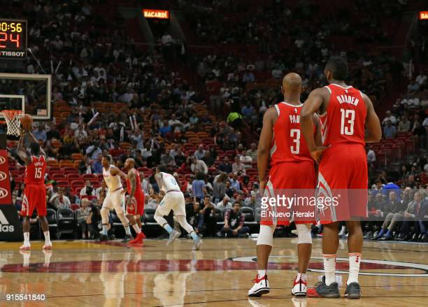 The Houston Rockets' Chris Paul talks with teammate James Harden as Clint Capela shoots a free throw during the first quarter against the Miami Heat...