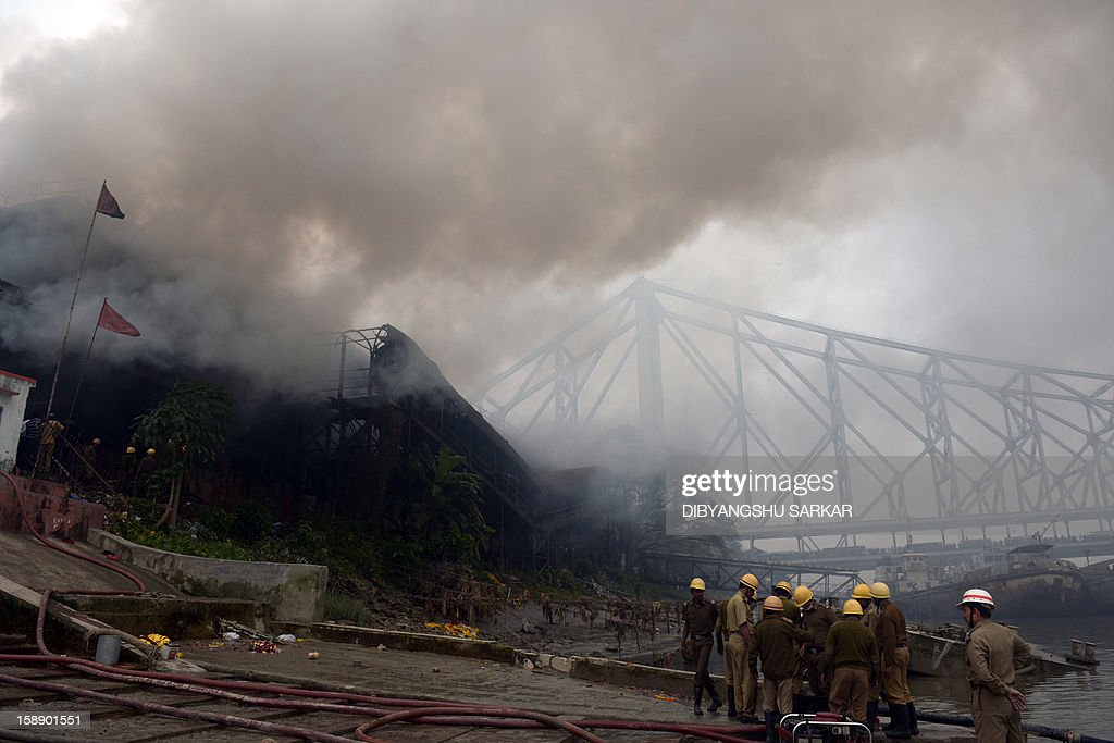 The Howrah bridge is pictured in the background as smoke rises from a burning godown in Kolkata on January 3, 2013. A fire destroyed a century old warehouse at Burrabazar, the commercial hub of the eastern region, destroying goods comprising cloth and other inflammable material, a report said. AFP PHOTO/Dibyangshu SARKAR