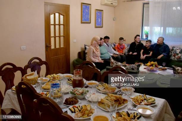 The Hoxha family sits at the table during the iftar the meal after sunset during the Islamic fasting month of Ramadan in Tirana on April 24 2020...