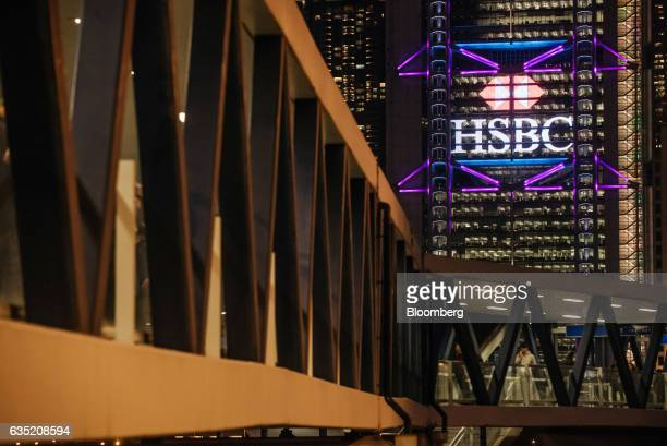 The HSBC Holdings Plc headquarters building stands illuminated behind a footbridge at night in the Central district of Hong Kong China on Monday Feb...