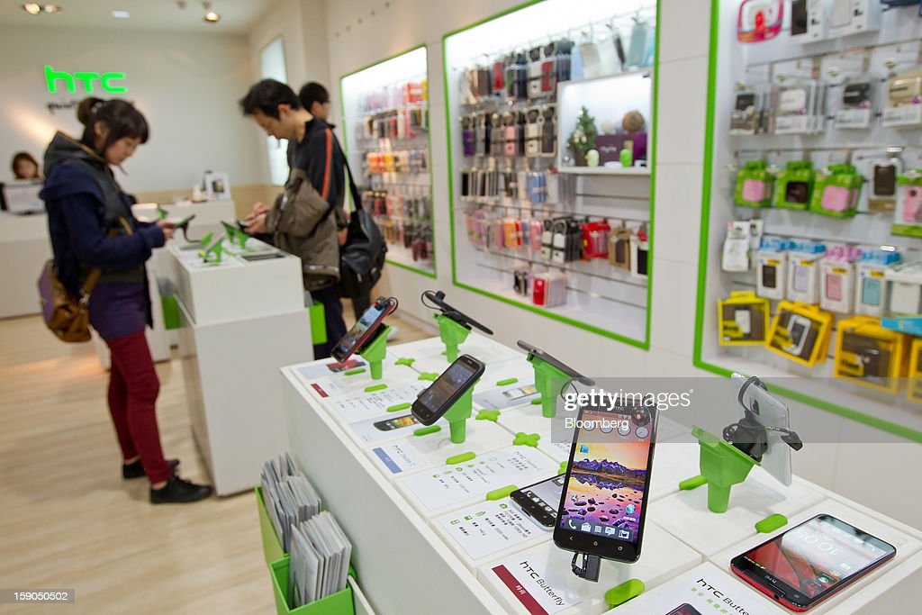 The HTC Corp. Butterfly smartphone, right, is displayed at one of the company's stores in Taipei, Taiwan, on Sunday, Jan. 6, 2013. HTC is scheduled to release fourth-quarter earnings on Jan. 7. Photographer: Maurice Tsai/Bloomberg via Getty Images