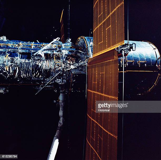 The Hubble Space Telescope before its relase from the space shuttle Discovery's remote manipulator system Solar array panels have been extended April...