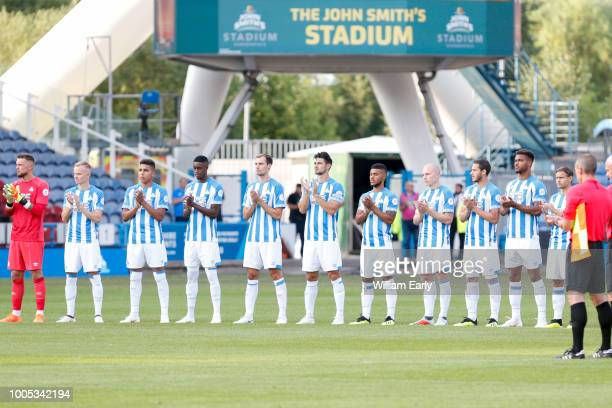 The Huddersfield Town players take part in a minutes applause in memory of Ray Wilson at John Smith's Stadium on July 25 2018 in Huddersfield England