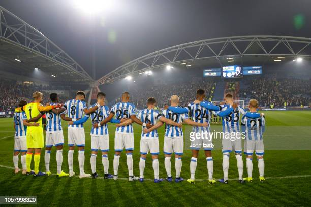 The Huddersfield Town team take part in a minutes silence to commemorate the life of Leicester City owner Vichai Srivaddhanaprabha before the Premier...