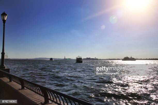 the hudson river waterfront as seen from the battery park city esplanade, with the statue of liberty far away in the background. new york city, usa - solar flare stock pictures, royalty-free photos & images