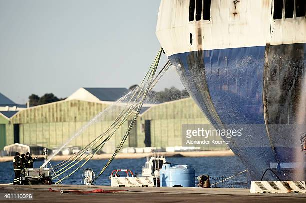 The hull of the burnedout ferry 'Norman Atlantic' is cooled by firemen during early morning as it stands moored in port during sunrise on January 07...