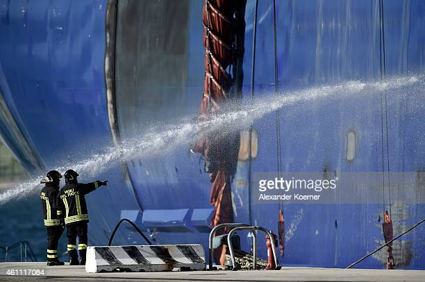 The hull of the burnedout ferry 'Norman Atlantic' is cooled by firemen as it stands moored in port during sunrise on January 07 2015 in Brindisi...