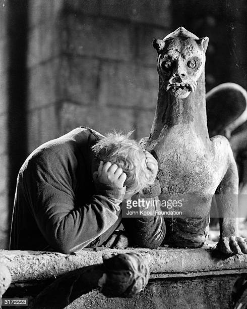 The hunchback Quasimodo played by Charles Laughton has only a gargoyle for company in 'The Hunchback of Notre Dame' directed by William Dieterle