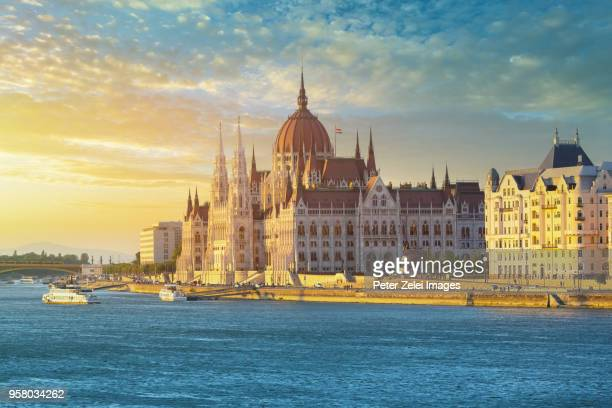 the hungarian parliament building in budapest at sunset - budapest stock pictures, royalty-free photos & images