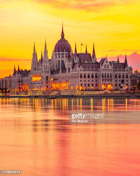 the hungarian parliament on the danube river at sunrise in budapest, hungary - royal palace budapest stock pictures, royalty-free photos & images