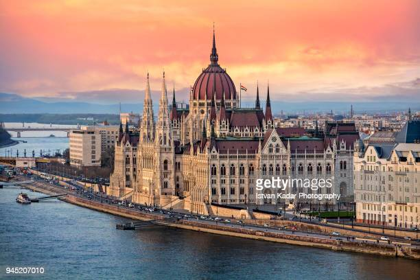the hungarian parliament on the danube river at sunset in budapest, hungary - hungary stock pictures, royalty-free photos & images