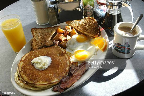 The Hungry Person's Breakfast with pancakes bacon two eggs wheat toast home fries orange juice and coffee
