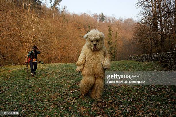 The hunter tries to catch the bear representing the evil as they perform during the Vijanera festival on January 8 2017 in Silio Cantabria province...