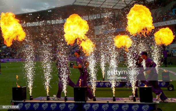 The Hurricanes run through flames and fireworks as they make their way onto the field during the Big Bash League match between the Hobart Hurricanes...