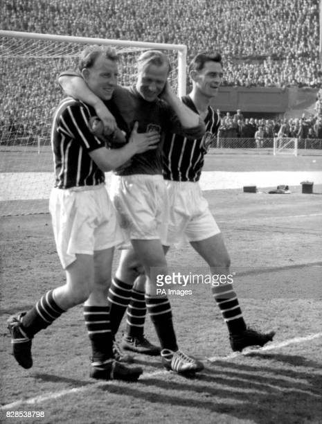 The hurt and dazed Bert Trautmann Manchester City's Germanborn goalkeeper is helped from the field by teammates Dave Ewing centre half and Bill...
