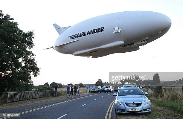 TOPSHOT The Hybrid Air Vehicles HAV 304 Airlander 10 hybrid airship is seen in the air over a road on its maiden flight from Cardington Airfield near...