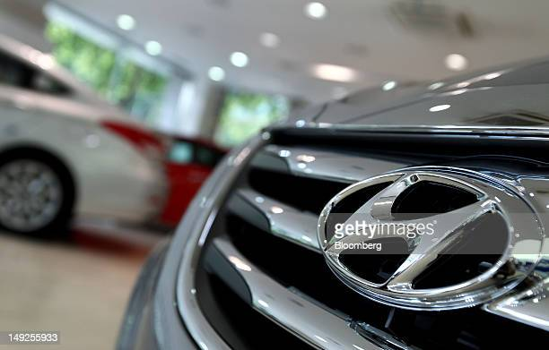The Hyundai Motor Co logo is displayed on a Sonata hybrid vehicle at a dealership in Seoul South Korea on Wednesday July 25 2012 South Korea's...