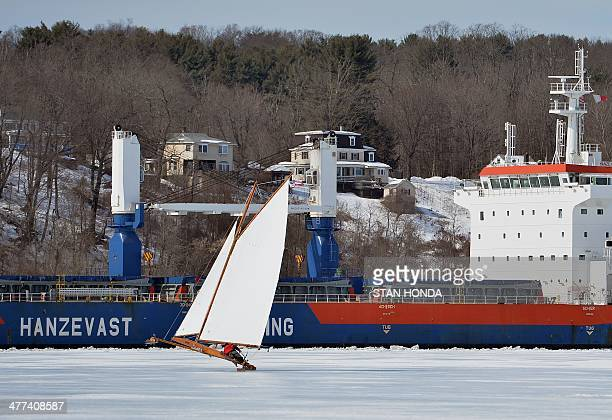 The ice boat Jack Frost rises up on one runner as it sails on a frozen Hudson River past a passing commercial ship the Hanze Goslar from the...