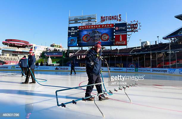 The ice crew sprays the ice in preparation for the 2015 Bridgestone NHL Winter Classic on December 30 2014 at Nationals Park in Washington DC The...