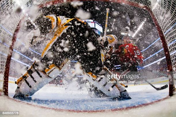 The ice sprays as Jonathan Toews of the Chicago Blackhawks approaches goalie MarcAndre Fleury of the Pittsburgh Penguins in the first period at the...