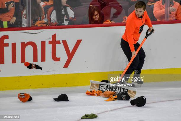 The Ice workers shovel hats of the ice during the NHL game between the Pittsburgh Penguins and the Philadelphia Flyers on April 22 2018 at the Wells...