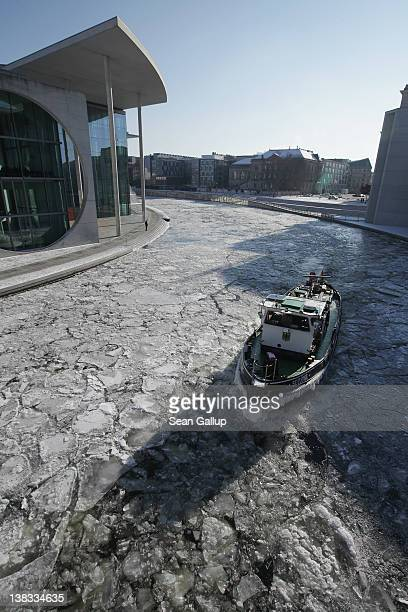 The icebreaker 'Seeloewe' makes its way through ice past government buildings on the Spree river on February 6 2012 in Berlin Germany Temperatures...